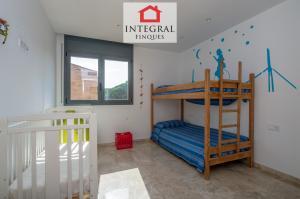 Chambre avec un lit superposé et un lit bébé, idéale pour des vacances avec des enfants.