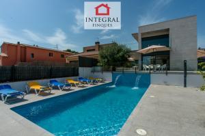 Villa avec une grande piscine, des chaises longues et tout le mobilier nécessaire pour passer des vacances idéales.
